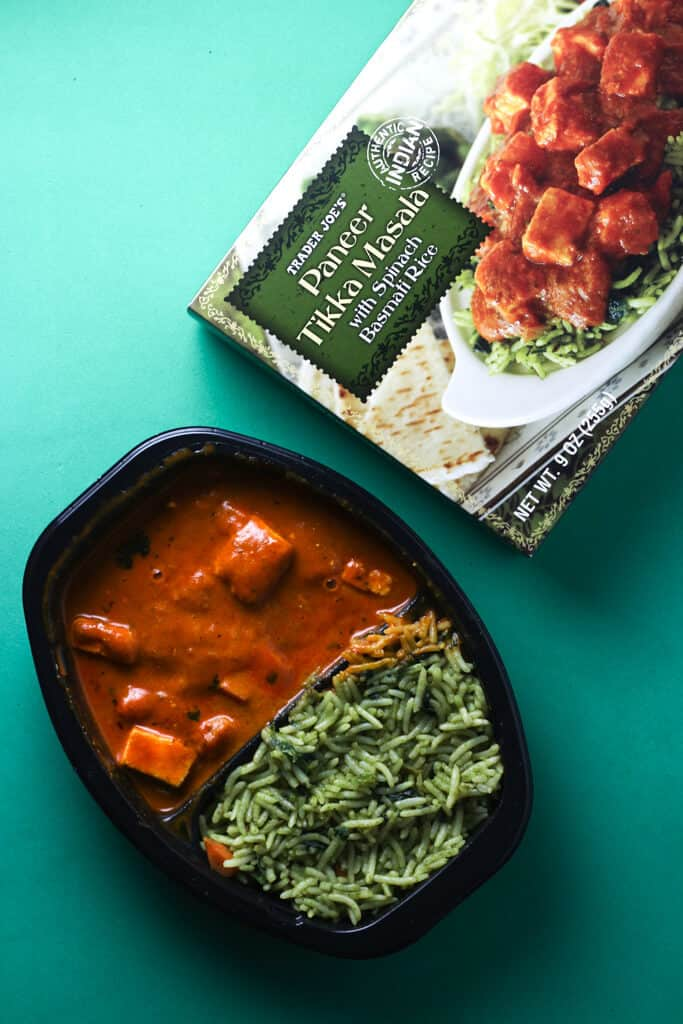 Trader Joe's Paneer Tikka Masala as prepared next to the original box on a green background.