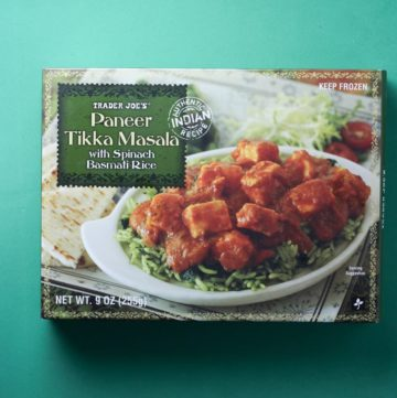 An unopened box of Trader Joe's Paneer Tikka Masala box on a green background