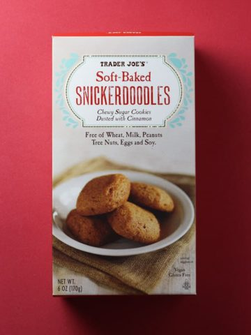 An unopened box of Trader Joe's Soft Baked Snickerdoodles box on a red background