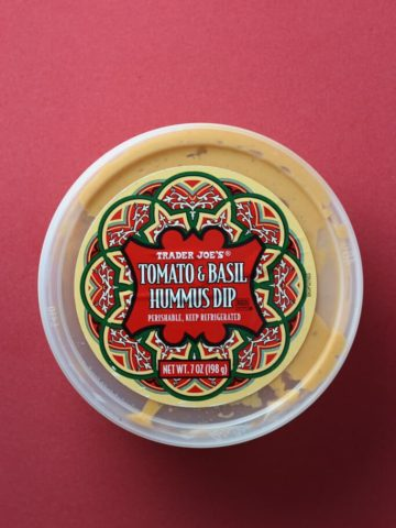 Trader Joe's Tomato and Basil Hummus Dip on a red background.