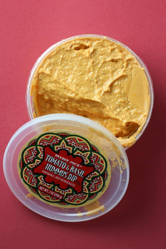 Trader Joe's Tomato and Basil Hummus Dip with an open package.