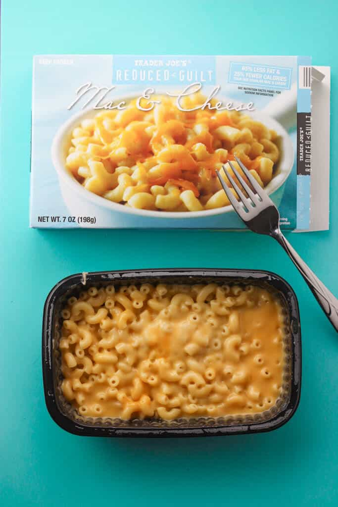 A fully cooked Trader Joe's Reduced Guilt Mac and Cheese cooked with a fork and the original box