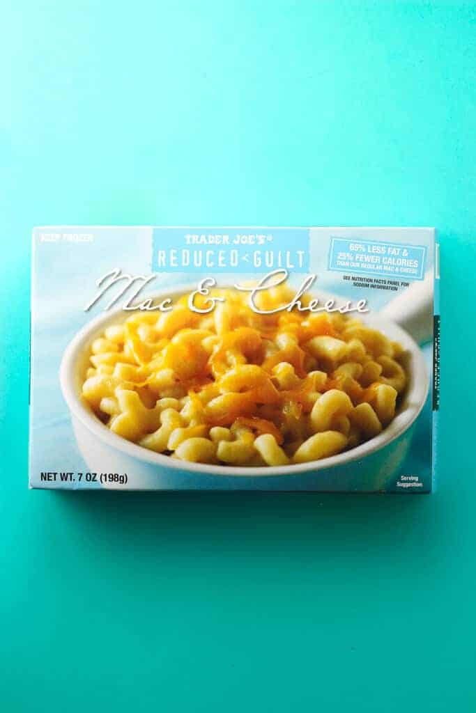 An unopened box of Trader Joe's Reduced Guilt Mac and Cheese on a blue background