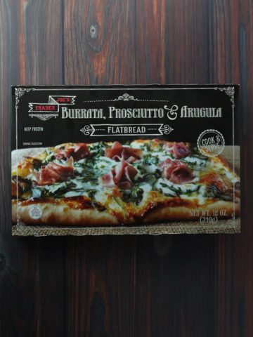 Trader Joe's Burrata, Prosciutto and Arugula Flatbread box on a dark wood surface