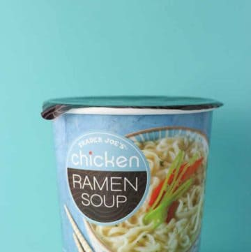 An unopened container of Trader Joe's Chicken Ramen Soup on a blue background