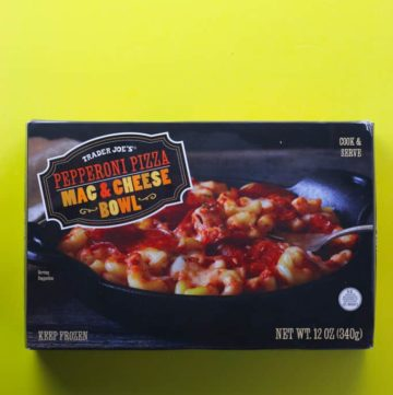 An unopened box of Trader Joe's Pepperoni Mac and Cheese Bowl on a yellow surface