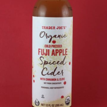 An unopened bottle of Trader Joe's Organic Cold Pressed Fuji Apple Spiced Cider with a red background