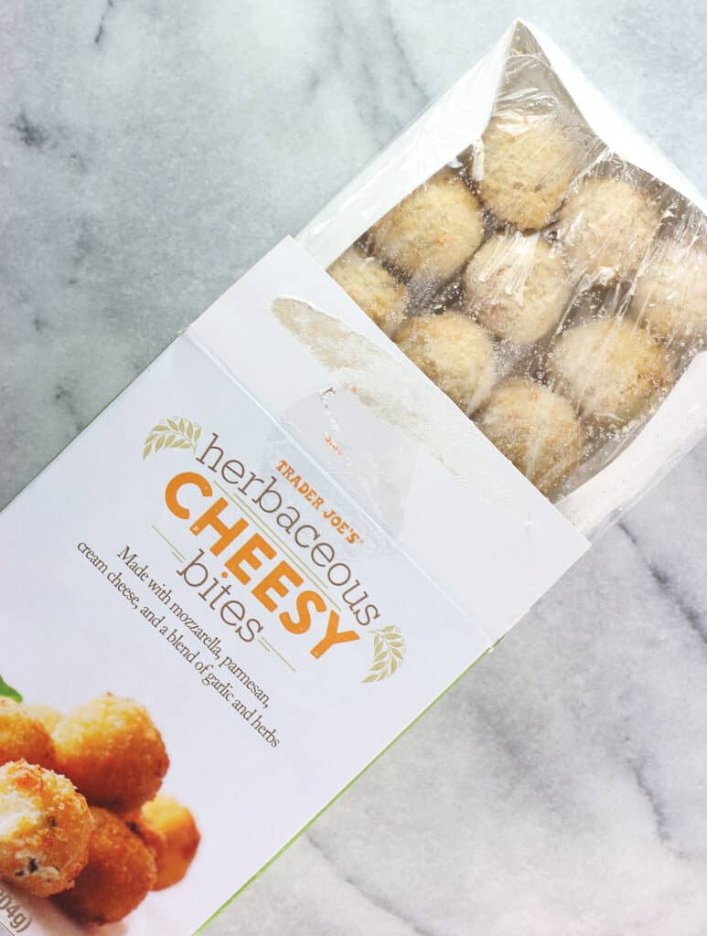 An opened box of Trader Joe's Herbaceous Cheesy Bites showing the contents of the box