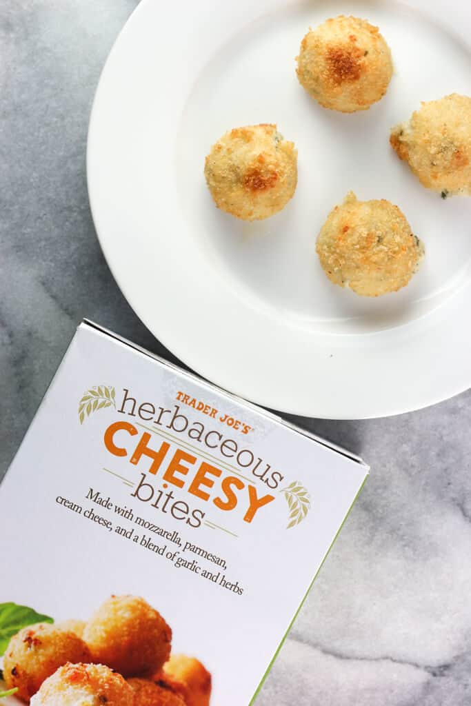 Four fully cooked Trader Joe's Herbaceous Cheesy Bites on a white plate with the empty box next to them