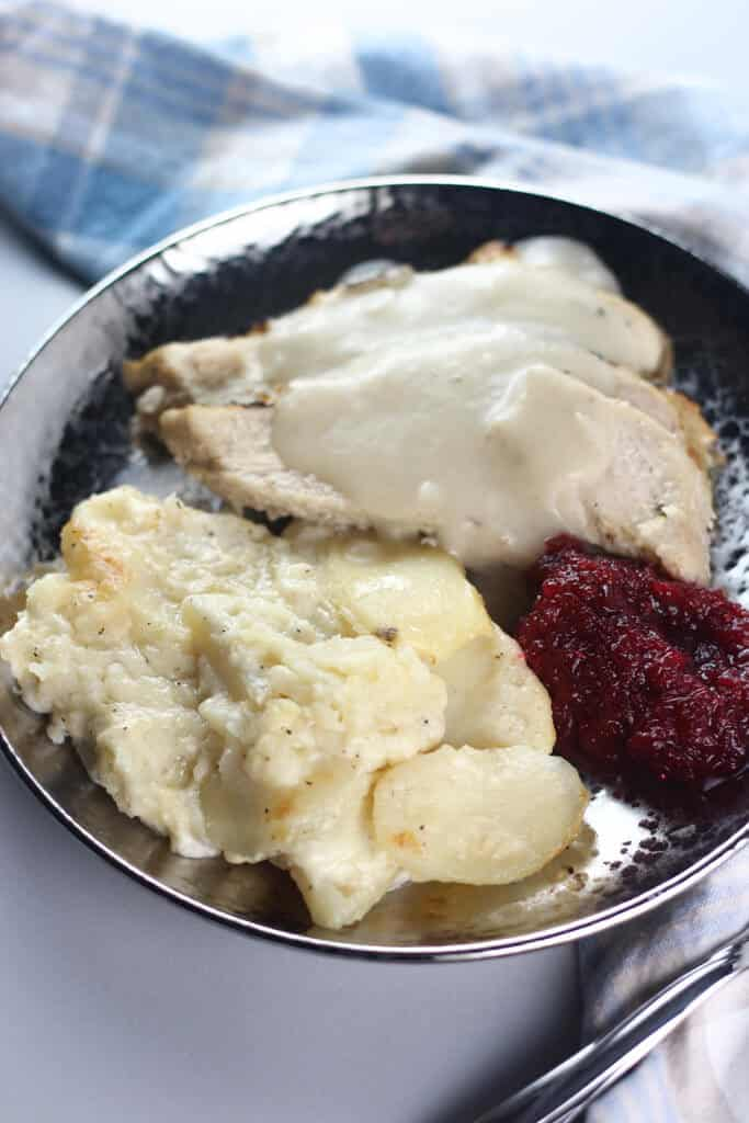 Trader Joe's Fresh Cranberry Orange Relish and Kettle Cooked Turkey Gravy on a plate with turkey and scalloped potatoes