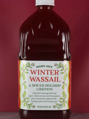 An unopened bottle of Trader Joe's Winter Wassail with a red back drop