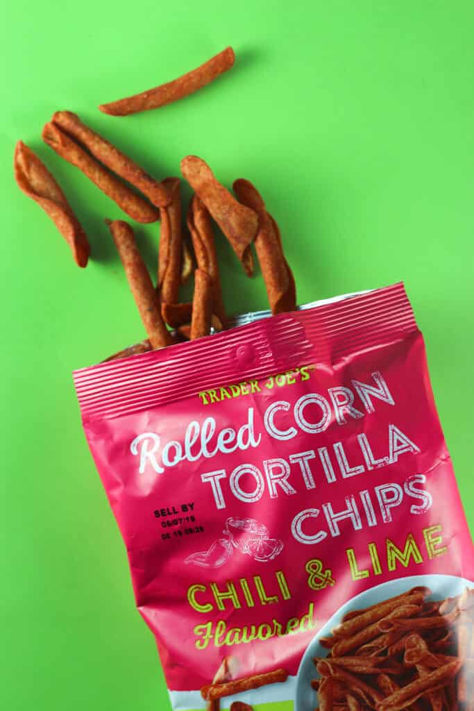 An opened bag of Trader Joe's Rolled Corn Tortilla Chips showing the chips on a lime green background