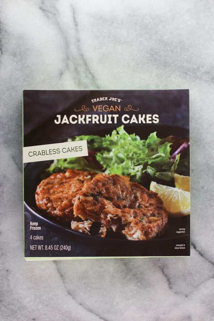 An unopened box of Trader Joe's Vegan Jackfruit Cakes on a marble background