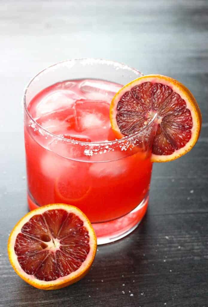 A backlit picture of a blood orange margarita garnished with blood oranges