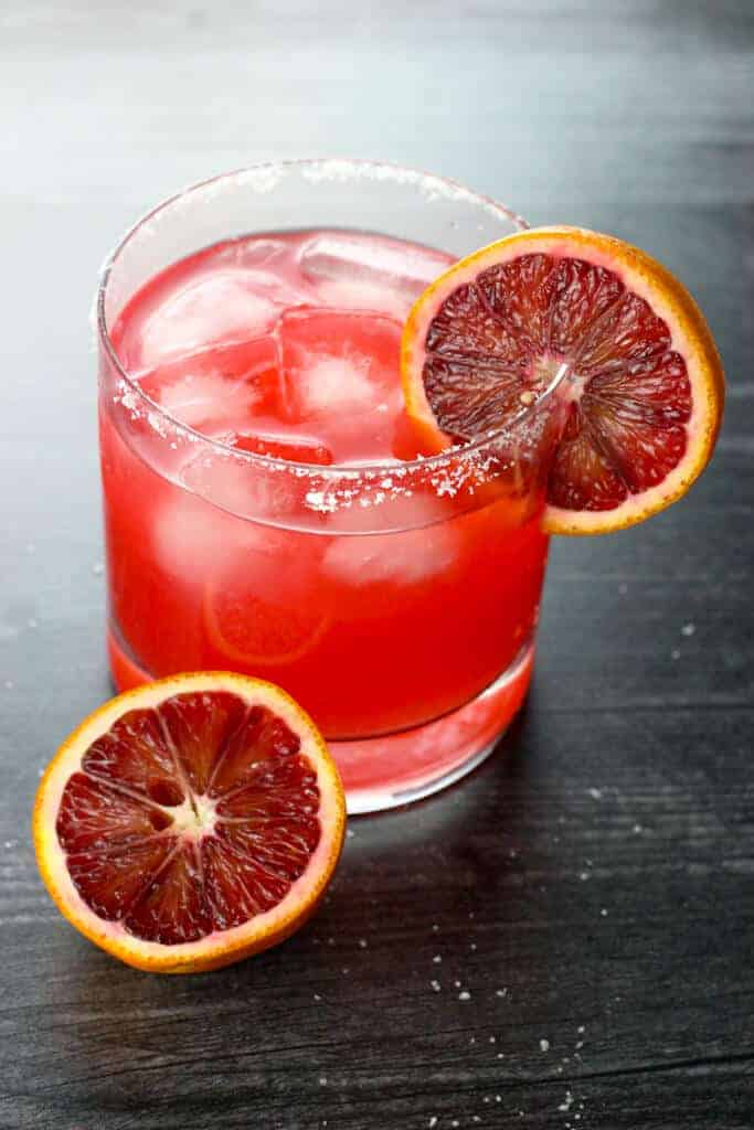 A blood orange margarita with garnish on a dark wooden surface