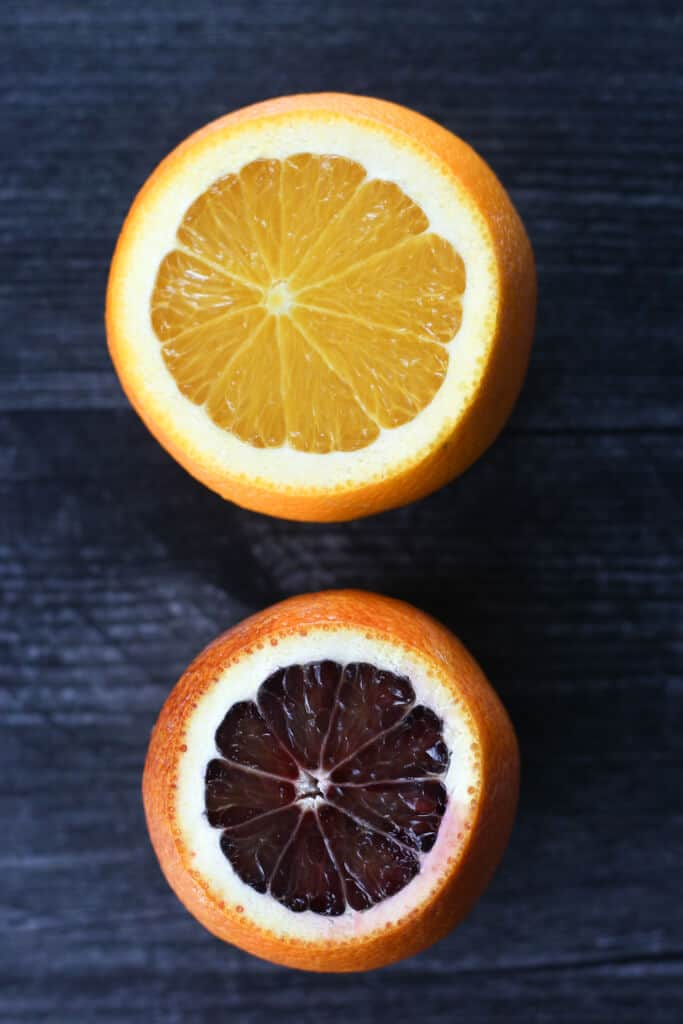 A navel orange sliced open compared to a moro blood orange