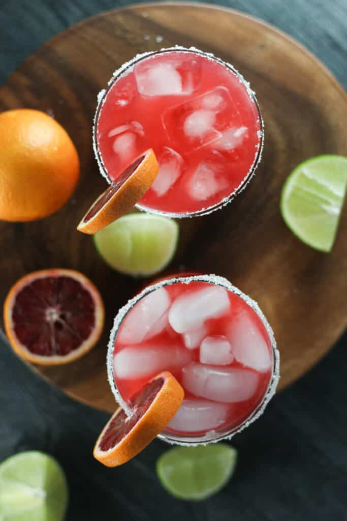 Two blood orange margaritas with cut fruit showing the difference ice makes.