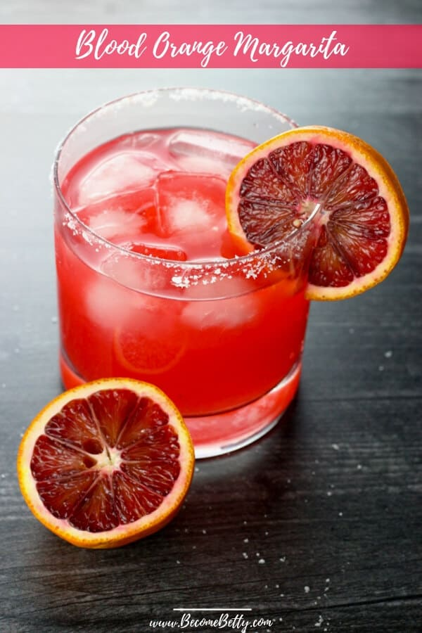 Blood Orange Margarita Pin for Pinterest featuring a bright red pink margarita with a salt rim and blood orange slices
