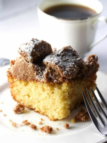 A slice of crumb cake with powdered sugar and a coffee cup in the background