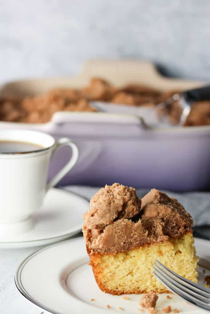 A slice of crumb cake with coffee and the baking dish on the background.
