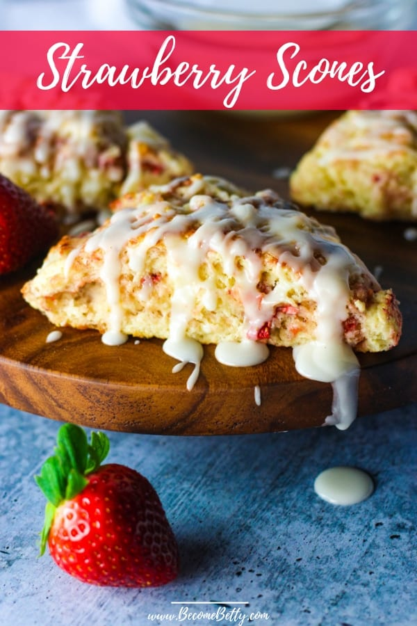 Strawberry scone with glaze on a wooden lazy susan with glaze dripping off the side pin for Pinterest