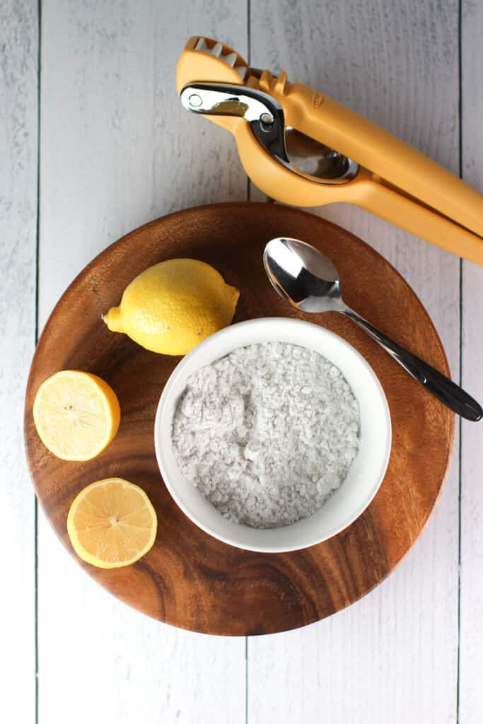 Ingredients needed to make a glaze: confectioners sugar and lemons with a juicer in the background and spoon for mixing