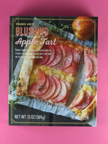 An unopened box of Trader Joe's Blushing Apple Tart on a pink background
