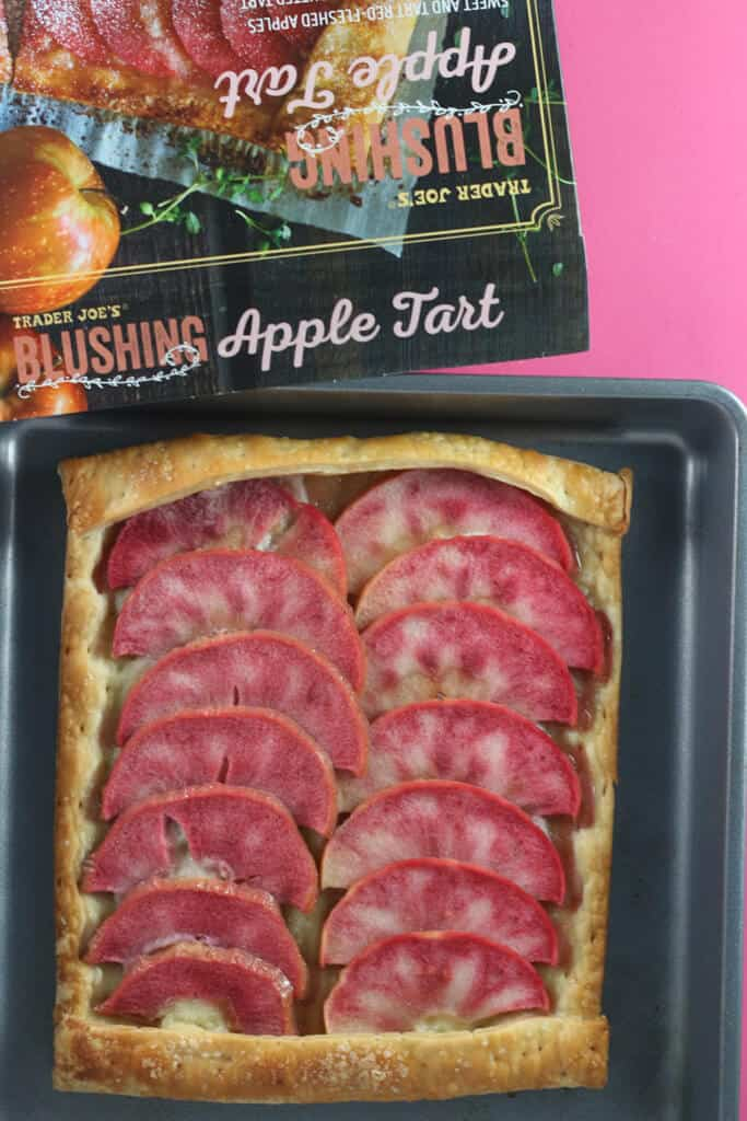 A fully cooked Trader Joe's Blushing Apple Tart on a baking sheet with the original box next to it