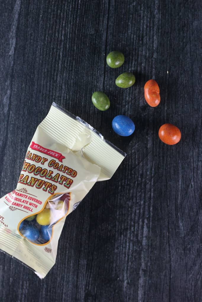 Trader Joe's Candy Coated Chocolate Peanuts out of the bag on a dark surface