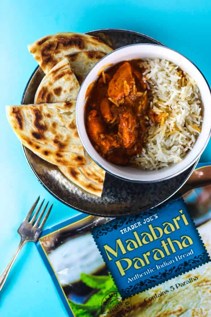 The opened bag of Trader Joe's Malabari Paratha with chicken tikka masala with rice on a silver plate