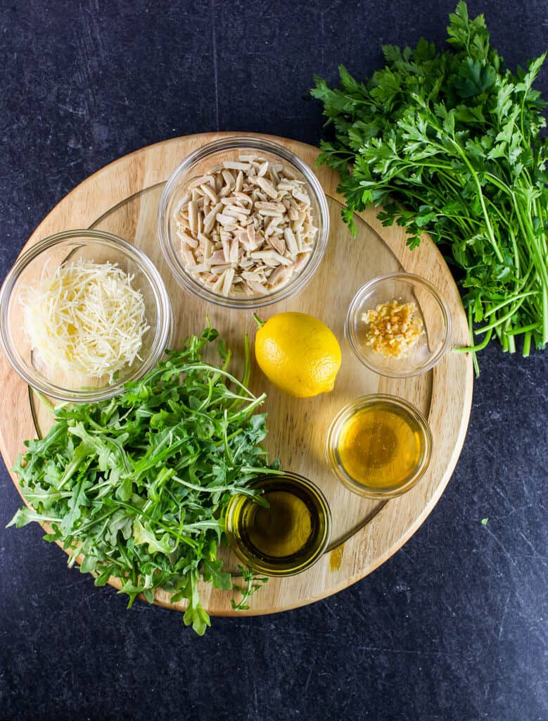Arugula, parmesan cheese, parsley, lemon, garlic, olive oil, vinegar, and almonds on a wooden lazy susan on a black background. All of these are ingredients going into the arugula pesto.