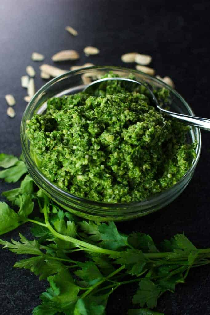 A finished pesto with parsley and almonds surrounding it.