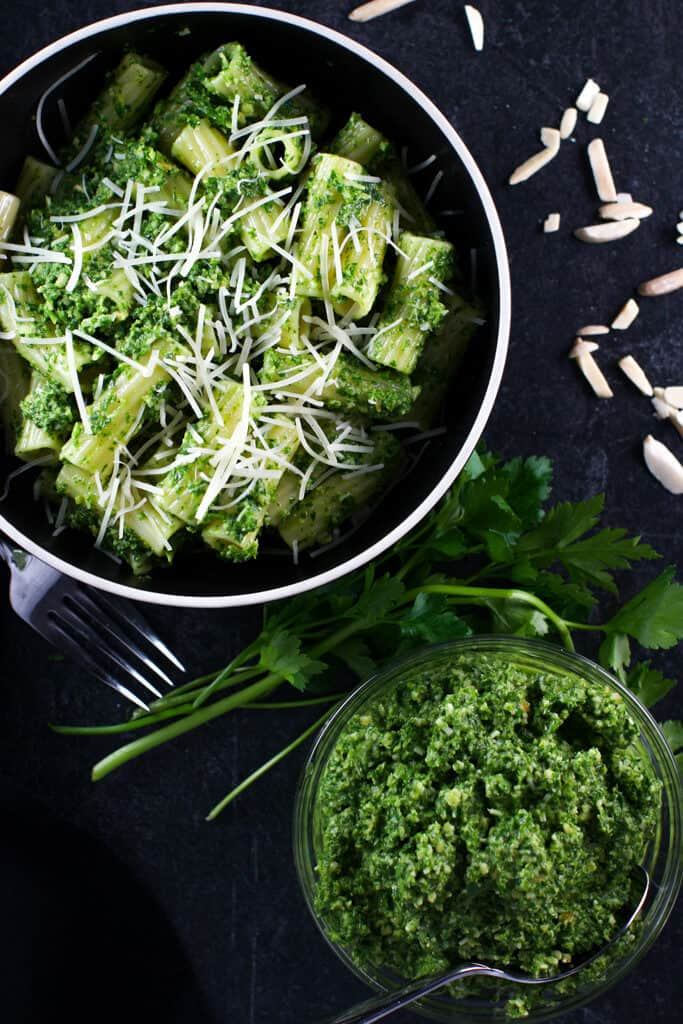 Finished arugula pesto with finished pesto in a bowl surrounded by almonds and parsley