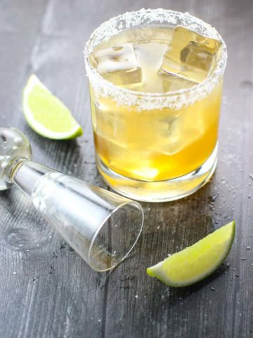 Cadillac Margarita fully prepared with empty shot glass, limes, and salt