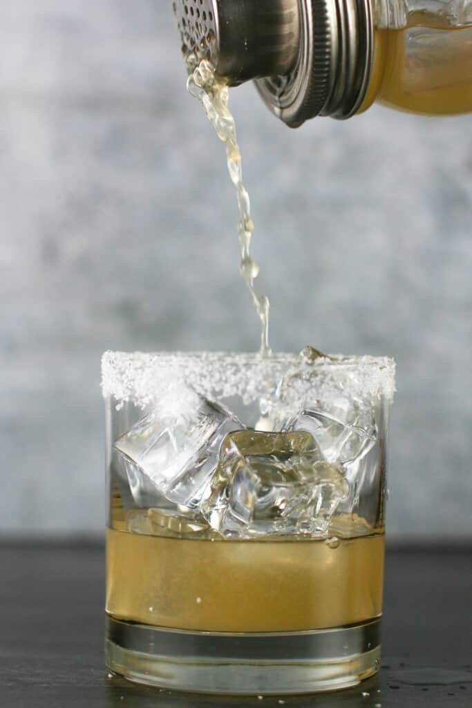 Pour shot of Cadillac Margarita going into a glass full of ice