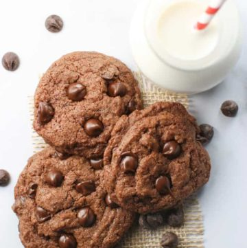 Chocolate Chocolate Chip Cookies with a glass of milk and straw next to it.