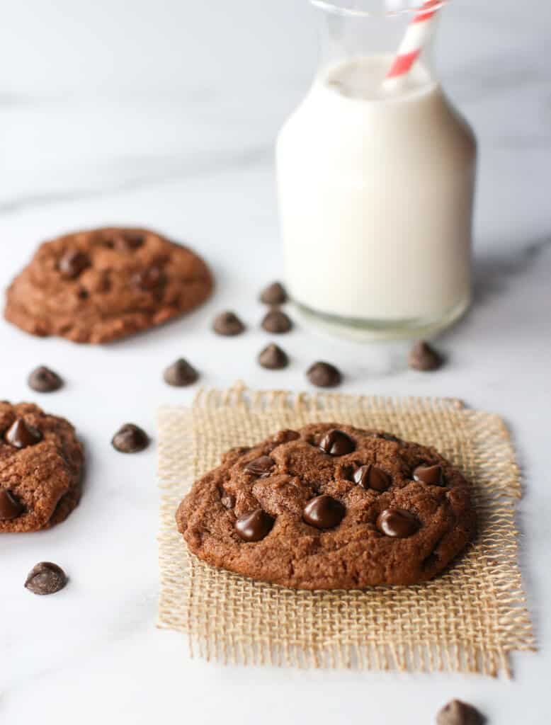 Chocolate Chocolate Chip Cookies with milk and chocolate chips on a marble surface