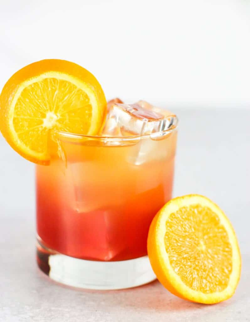 A beautifully layered Malibu Bay Breeze garnished with an orange wedge