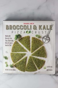 An unopened box of Trader Joe's Broccoli and Kale Pizza Crust on a marble surface