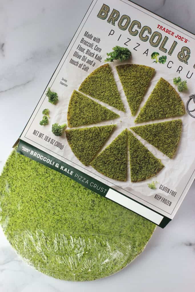 An opened box of Trader Joe's Broccoli and Kale Pizza Crust showing the green crust