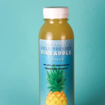 An unopened bottle of Trader Joe's Cold Pressed Pineapple Juice with a blue background.