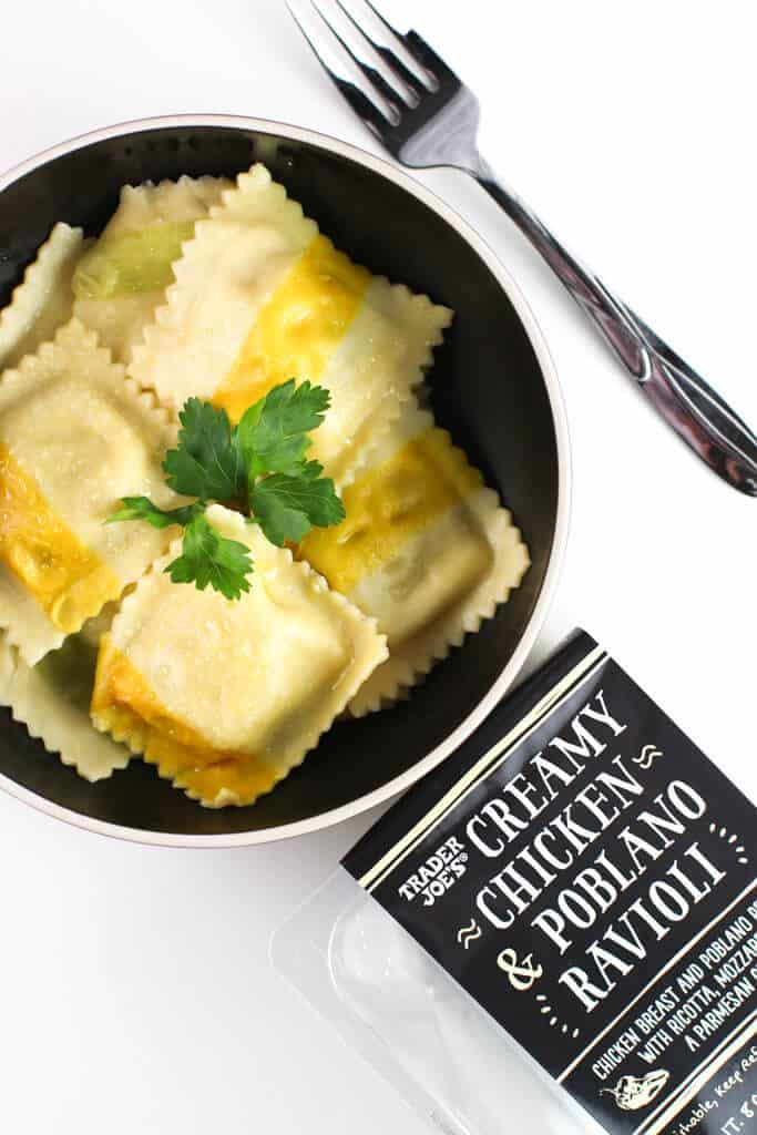 Trader Joe's Creamy Chicken and Poblano Ravioli fully cooked in a black bowl next to the empty packaging