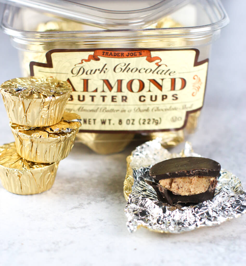 Trader Joe's Dark Chocolate Almond Butter Cups package open with one candy open and with a bite mark showing the inside