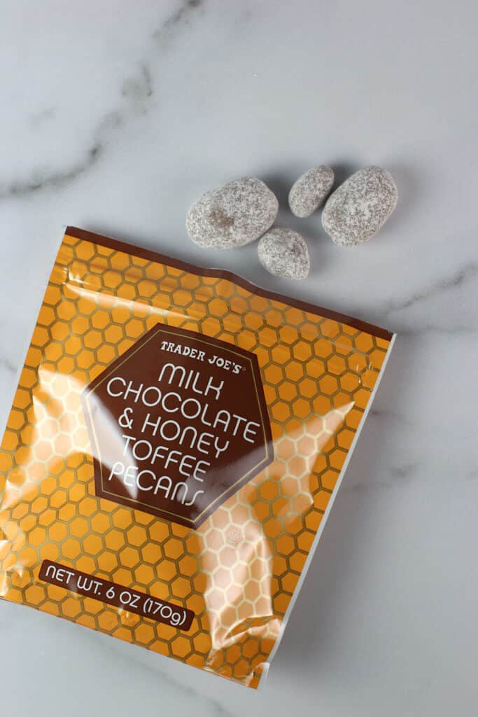 An opened bag of Trader Joe's Milk Chocolate and Honey Toffee Pecans showing the chocolates dusted in powdered sugar
