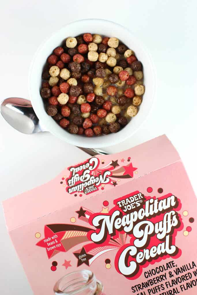 Trader Joe's Neapolitan Puffs Cereal in a bowl with a spoon next to the original box