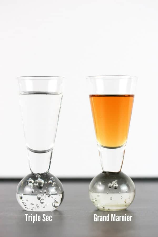 A side by side of two shot glasses. One contains a clear Triple Sec. The other contains a shot of Grand Marnier which is more orange.
