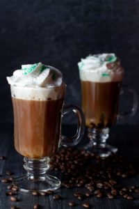 Two Irish Coffees on a dark surface surrounded by coffee beans and topped with whipped cream