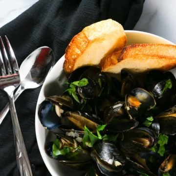 A white bowl full of Mussels in White Wine Sauce served with bread with a spoon and fork on a black napkin