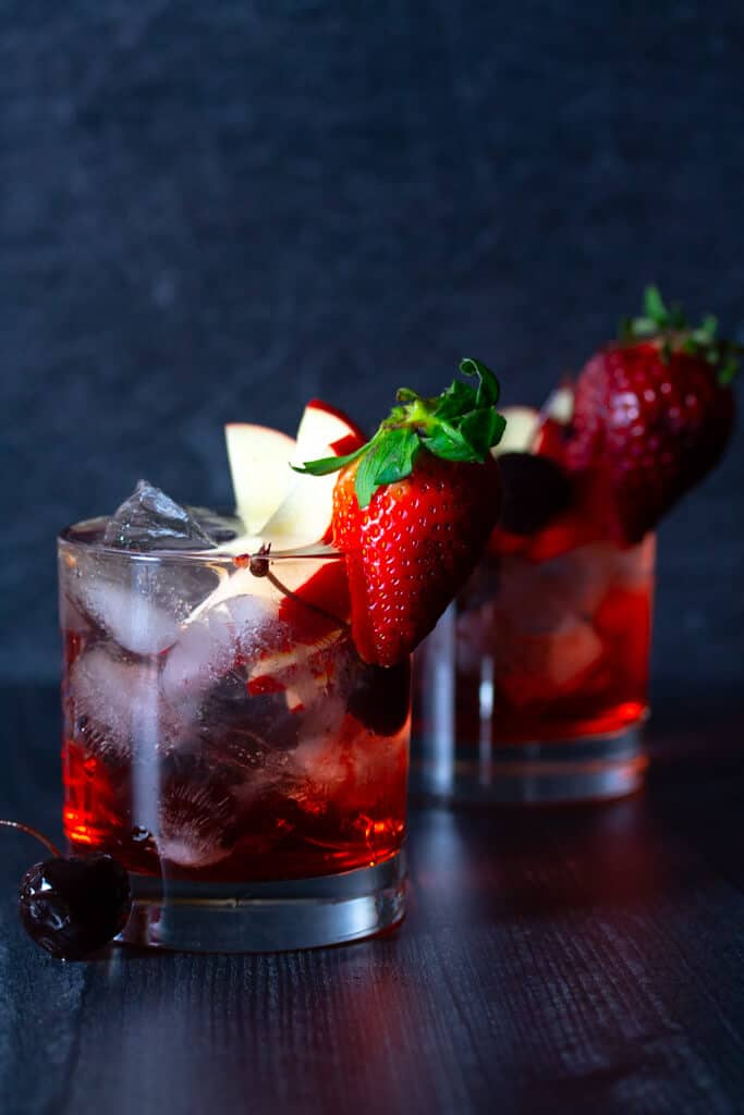 Two finished Red Russian cocktails on a dark surface with garnishes like apples and strawberries and cherries.