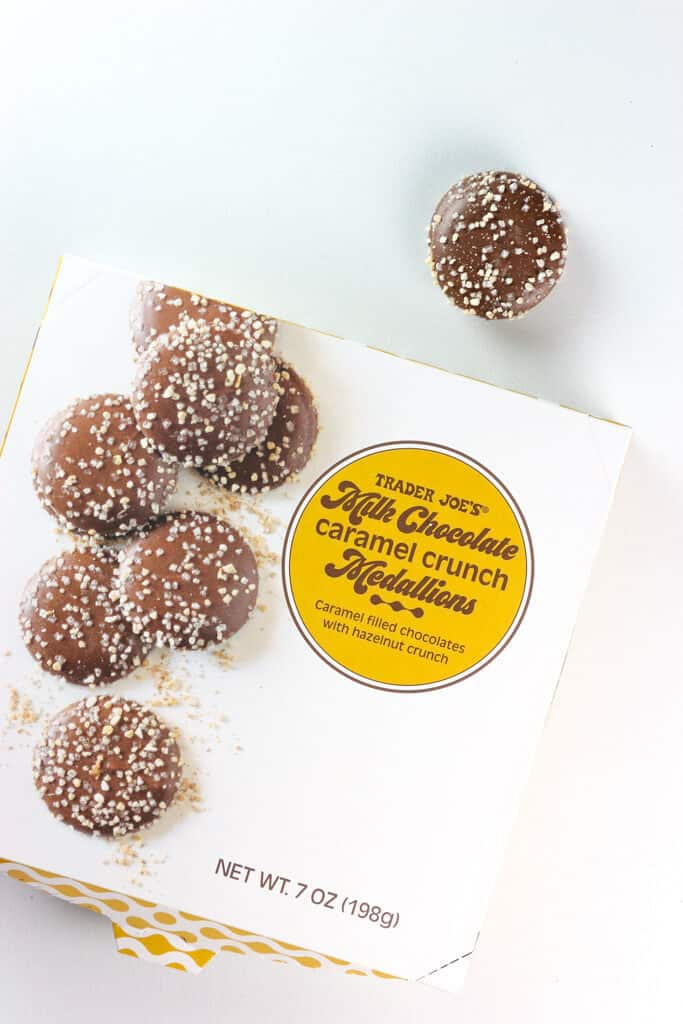 Trader Joe's Milk Chocolate Caramel Crunch Medallions with one candy out of the package